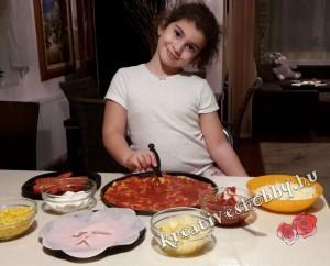 Pizza: megkenjük a tésztát a szósszal